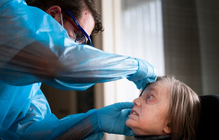 Thuiszorgmedewerker Arjo Verheijen helpt coronapatient mevrouw Van de Poll met haar oogdruppels. Beeld Freek van den Bergh / de Volkskrant