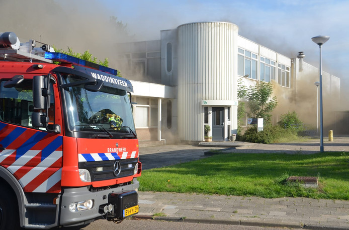 Aan alle kanten komt er rook uit het gebouw.