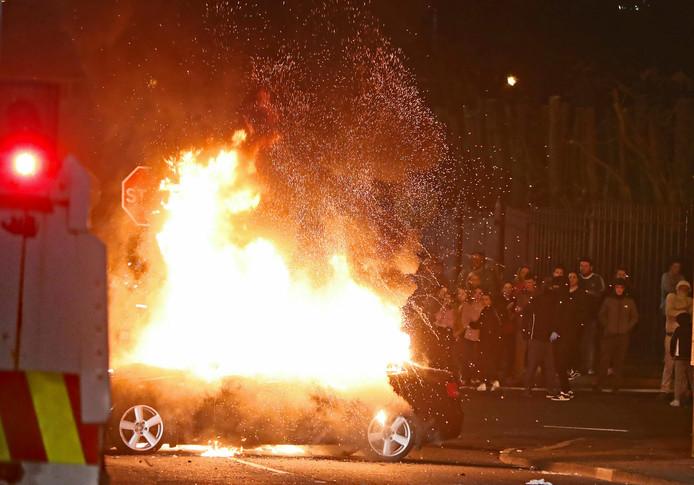 Een auto gaat in vlammen op tijdens rellen in het Noord-Ierse Londonderry.