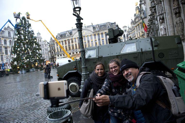 Op de Grote Markt, waar net een grote kerstboom wordt versierd, maken toeristen een selfie voor een legervoertuig van het Belgische leger opgesteld vanwege verhoogde terreurdreiging in de Belgische hoofdstad. Beeld anp