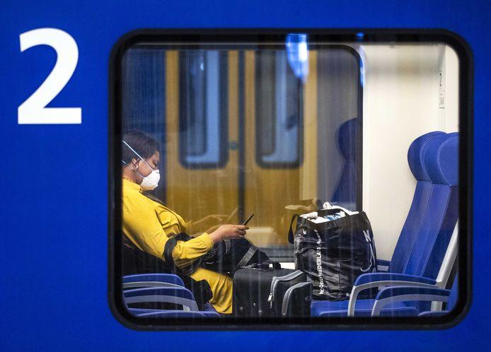 Een reiziger met een mondkapje op in de trein.