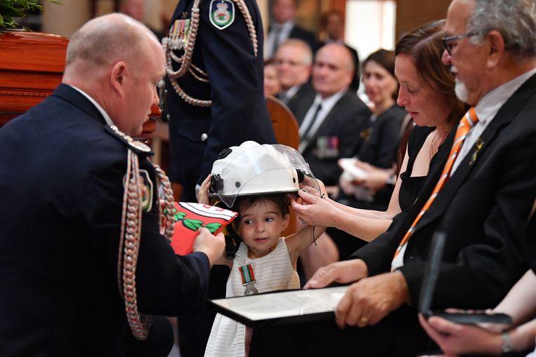 Brandweercommandant Shane Fitzsimmons spelde kleine Charlotte (negentien maanden oud) een erepenning op voor het dappere werk van haar vader.