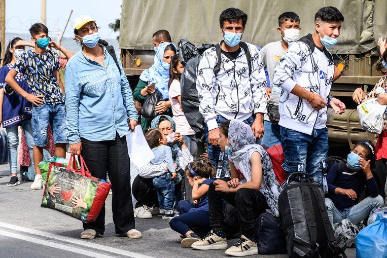 Vluchtelingen wachten op bussen bij het Kara Tepe kamp op Lesbos, om te vertrekken naar de haven.  Beeld EPA