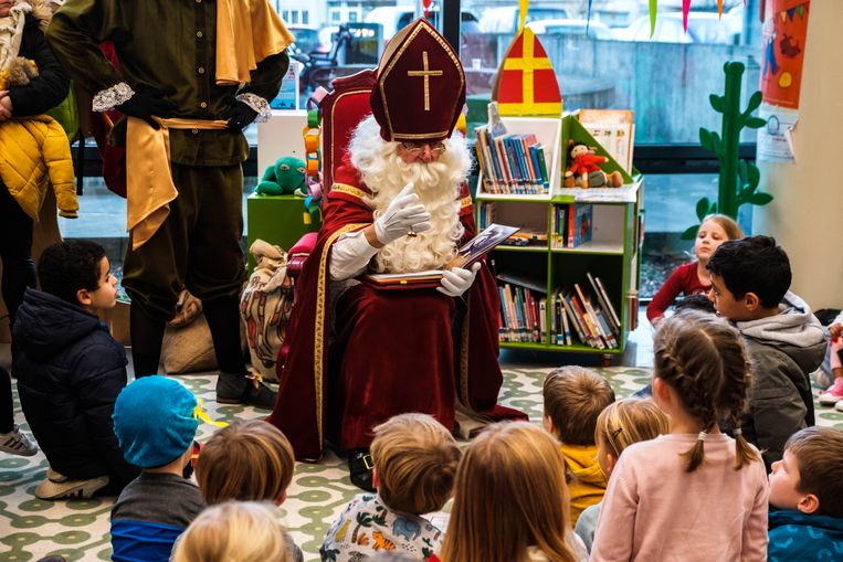 Sinterklaas leest voor in de bibliotheek.