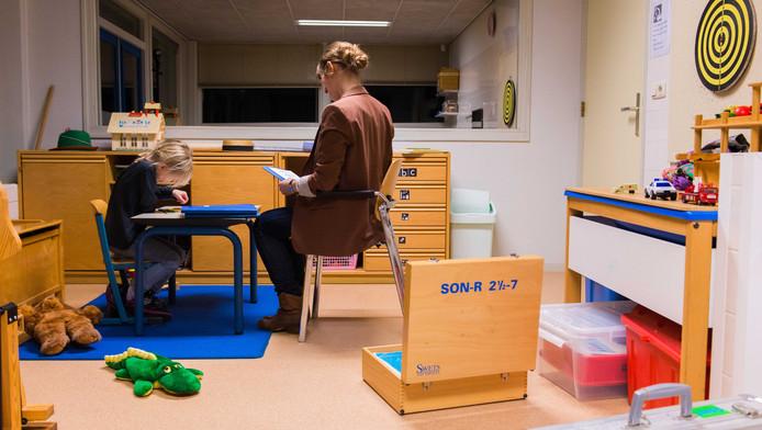 Een hulpverlener neemt een test af bij een meisje. Vanaf 1 januari 2015 zijn gemeenten verantwoordelijk voor de jeugdzorg.