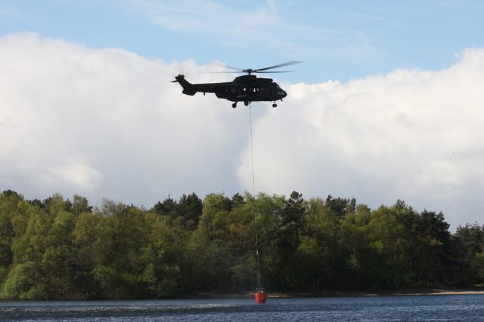 Beeld ter illustratie: een Cougar helikopter 'tankt' bluswater.