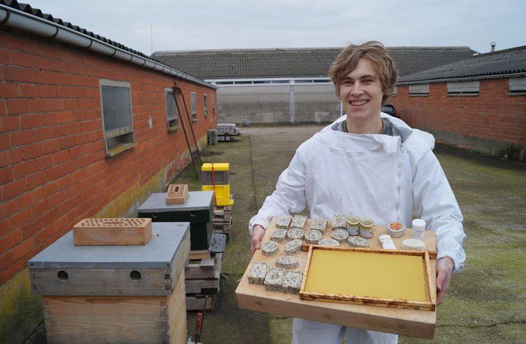 Imker Robbe Dhulster met een paar van zijn zelfgemaakte bijenwasproductjes.