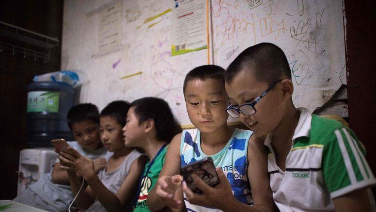 Kinderen spelen spelletjes op hun smartphone in een migrantengemeenschap in de buitenwijken van Peking, 17 augustus. Beeld afp