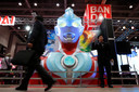 Bezoekers aan een entertainmentbeurs in Japan lopen langs een reusachtige buste van Ultraman