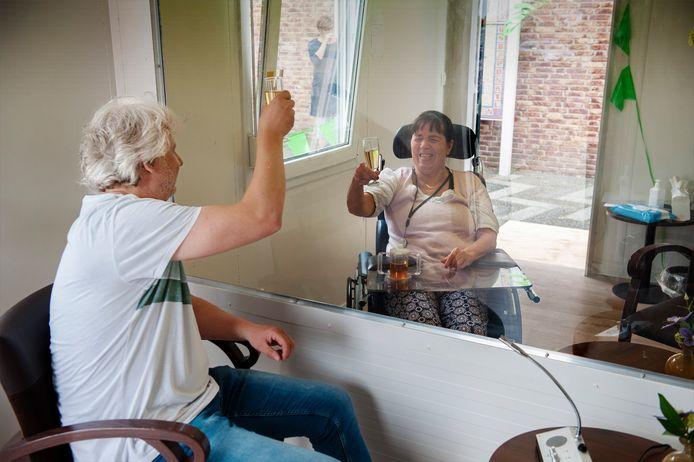 Paula en Marc Smits toasten op hun eerste bezoek  aan de corona-container bij zorgcentrum De Zandley in Drunen.