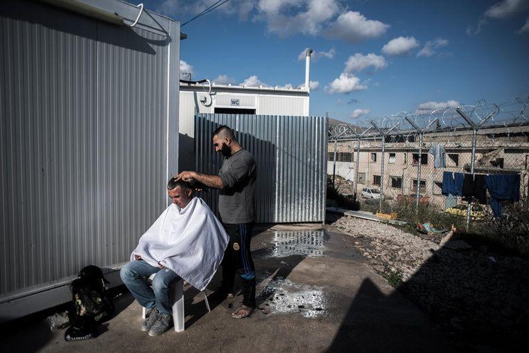 Een Syrische kapper doet zijn werk in Vial. 'Ik wil geen voedsel of eten, ik wil een leven.' Beeld Joris van Gennip / de Volkskrant