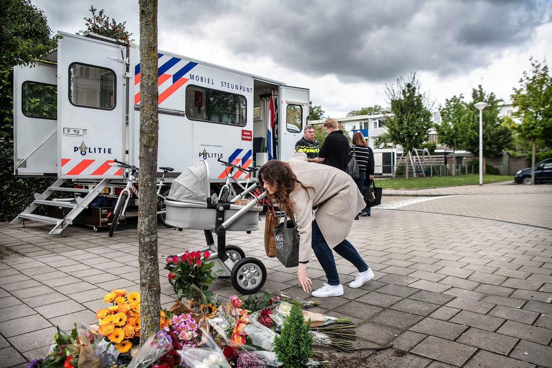 Mensen leggen bloemen neer in de straat waar advocaat Derk Wiersum werd doodgeschoten. Beeld Guus Dubbelman / de Volkskrant