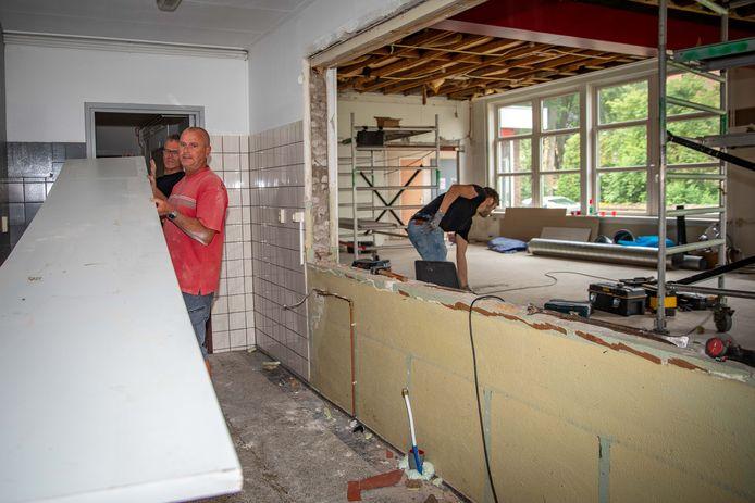 Vrijwilligers Dave, Peter en Thomas (vlnr) helpen bij de verbouwing van het dorpshuis in Schore.