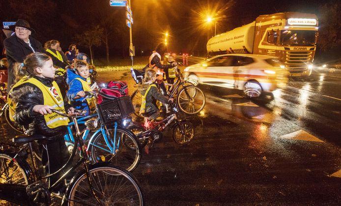 Schoolkinderen uit Haarle laten wethouder Jelle Beintema zien hoe moeilijk het is om met de fiets veilig de N35 over te steken.