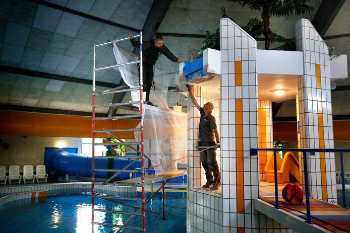 Plekken waar betonrot zit, worden vanaf een steiger in het bad aangepakt. De directie van het Caribabad in Gorinchem liet tijdens de sluiting het nodige onderhoud uitvoeren.
