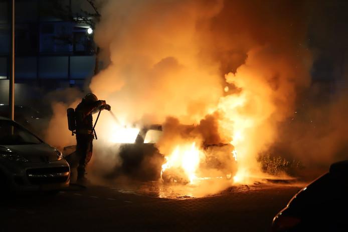 De brandweer blust een brandende auto aan de Estafetteweg in Gouda. Het voertuig brandde geheel uit.