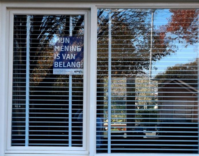 Een Rielenaar geeft met een poster aan dat hij gehoord wil worden over het complex voor arbeidsmigranten.