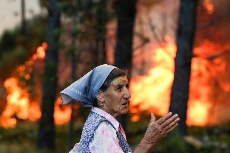 Een inwoner van het gebied bekijkt de bosbranden