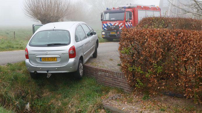 De automobiliste van deze auto maakte ruimte voor een naderende vrachtwagen (niet de brandweerwagen op de foto), maar reed daarbij half de greppel in.