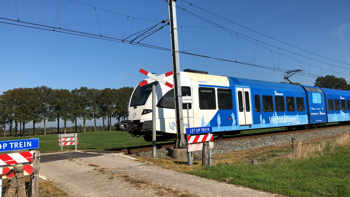 Arriva-trein passeert de onbewaakte spoorwegovergang.