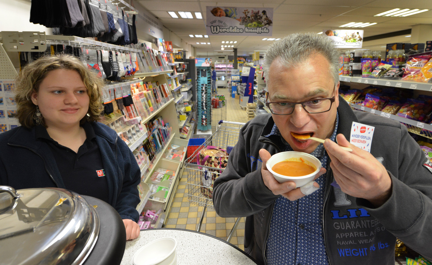 Hein van Lith proeft in de MCD in Kapel-Avezaath de Barstensvolsoep tegen voedselverspilling uit handen van Kristel van Est.