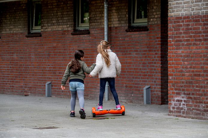 Kinderen spelen op straat op een hoverboard
