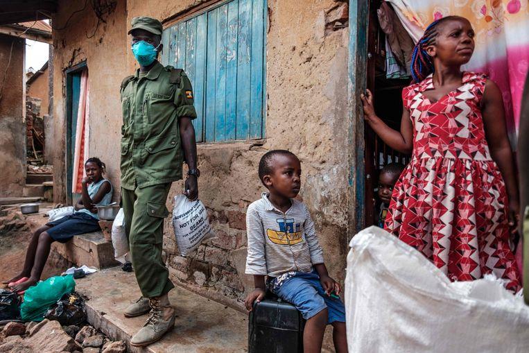 Een paramilitaire groep die uit burgers bestaat deelt voedsel uit in Kampala. Oeganda distribueert voedsel onder 1,5 miljoen kwetsbare mensen die zijn getroffen door de strenge lockdown. Beeld AFP