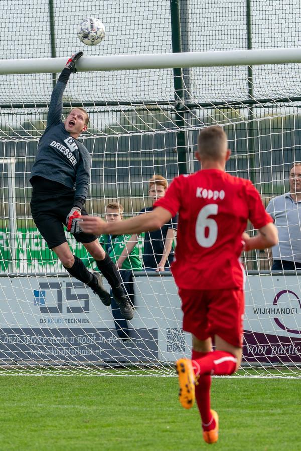 Jamie Dekkers tiks de bal over de lat. Cornelisse, met op het shirt 'Koppo', kijkt de bal na.
