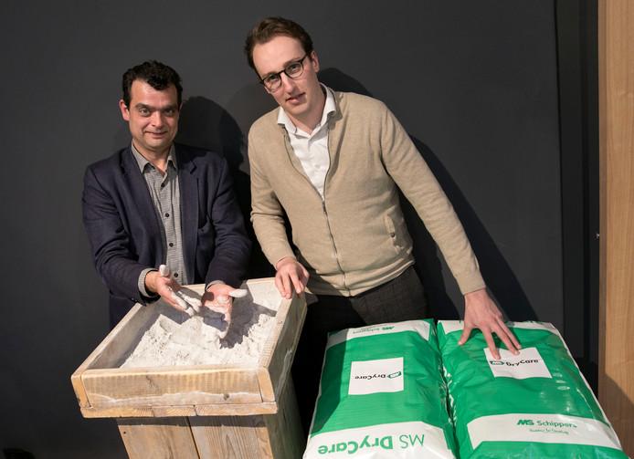 Harrie Schippers (l) en Constantijn Viezee van MS Schippers bij een bak en zakken met biologisch droogpoeder voor ligplaatsen voor rundvee en varkens en voor nesten voor kippen.