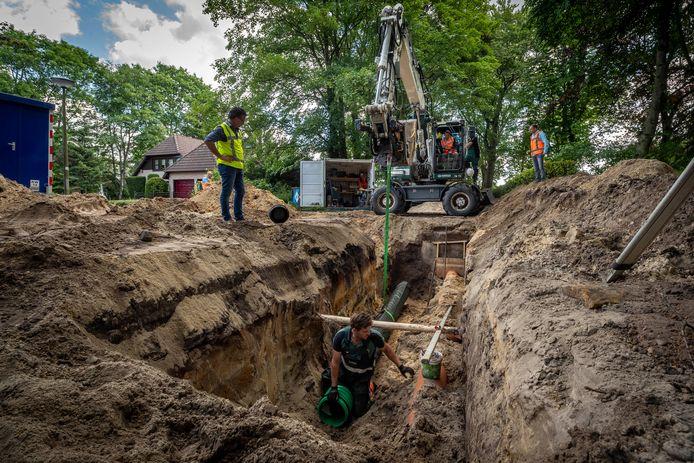 Gecoacht door een kraanmachinist laat de Woensdrechtse wethouder Jeffrey van Agtmaal een infiltratiebuis voor regenwater in de bodem zakken aan de Sparrenlaan in Putte. Dat moet helpen in de strijd tegen overlast bij hoosbuien.
