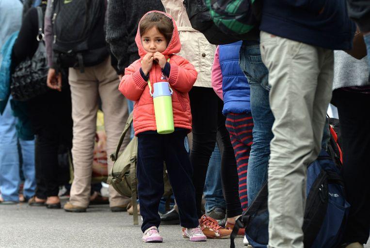 Een meisje wacht met andere vluchtelingen op een medische controle in München. Beeld null