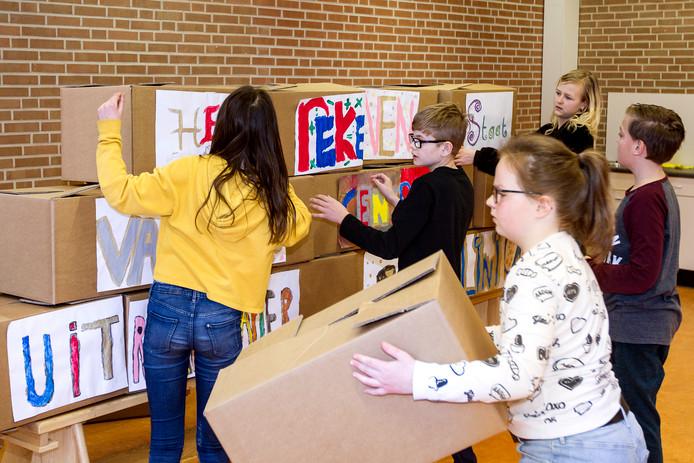 Leerlingen zijn druk in de weer met verhuisdozen, niet alleen om mee te sjouwen, maar ook om sommetjes mee te oefenen.