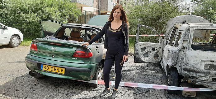 Duska Samardzic tussen twee uitgebrande auto's. De groene auto is van haar.