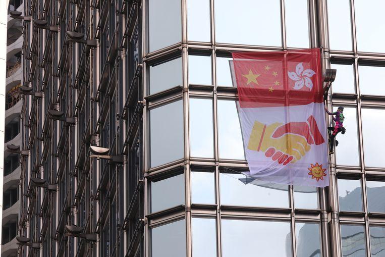 De 'Franse Spiderman', Alain Robert, beklom gisteren de wolkenkrabber Cheung Kong Center in Hongkong. Daar hing hij een spandoek op waarop de Chinese vlag en die van Hongkong samen te zien zijn, met een gele hand die een rode schudt, een teken van vrede. In Hongkong zijn al weken protesten tegen de regering.   Beeld EPA