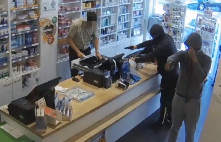 De overvallers houden de apotheker onder vuur terwijl die zijn kassa leegmaakt.