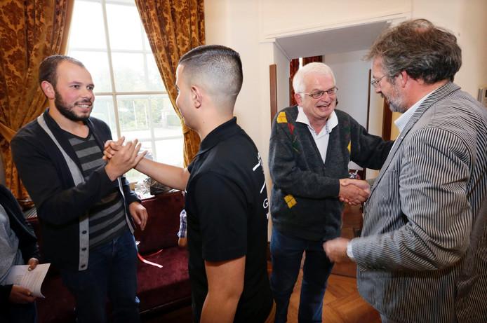 Pastor Jan Hopman en Farid Bouchlaghmi worden gefeliciteerd nadat Hopman uit handen van burgemeester Depla de bredase vredesprijs heeft ontvangen. Bouchlaghmi was de andere genomineerde.