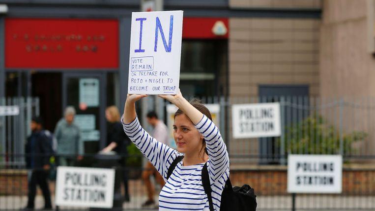 Een jonge Britse vrouw voert campagne tegen een Brexit bij de ingang van een stembureau. Beeld afp