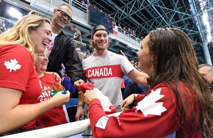 De Candese zwemster Penny Oleksiak (r) viert haar gouden medaille op de 100 meter  vrij op de Spelen vanTokio met haar familie.
