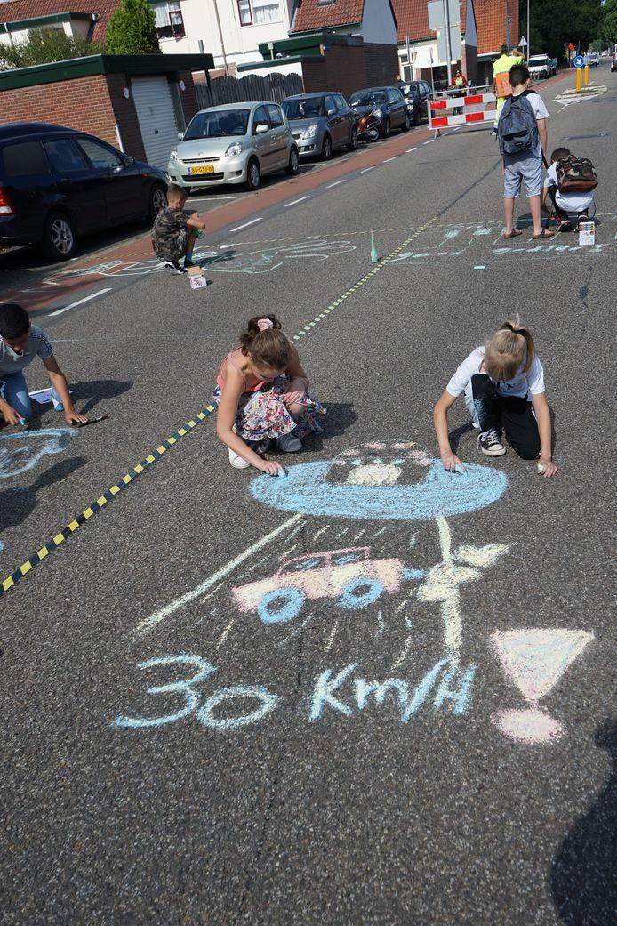 Kinderen delen in het Soesterkwartier een 'bekleuring' uit.