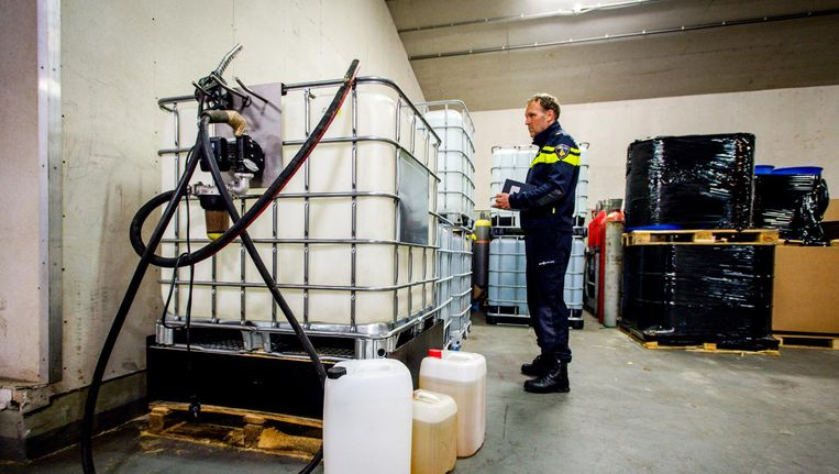 Een politieagent bekijkt chemicaliën die zijn aangetroffen in een bedrijfspand. Beeld anp