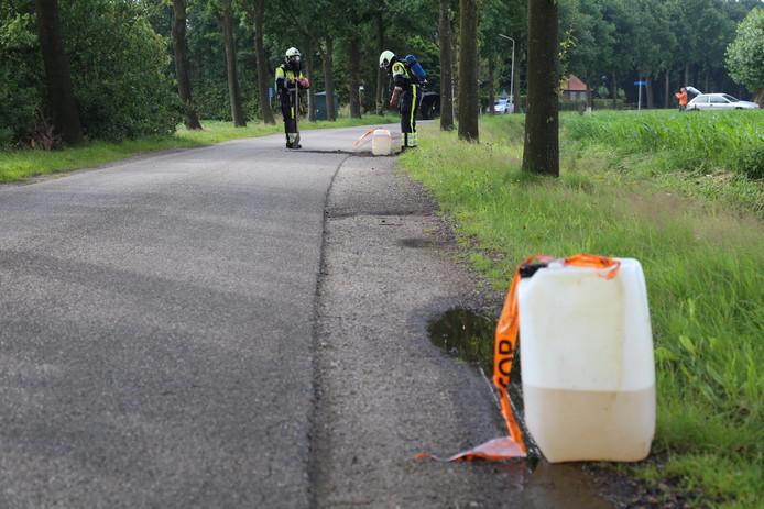 De brandweer controleert de vaten op de Wooijstraat in Herpen op gevaarlijke stoffen