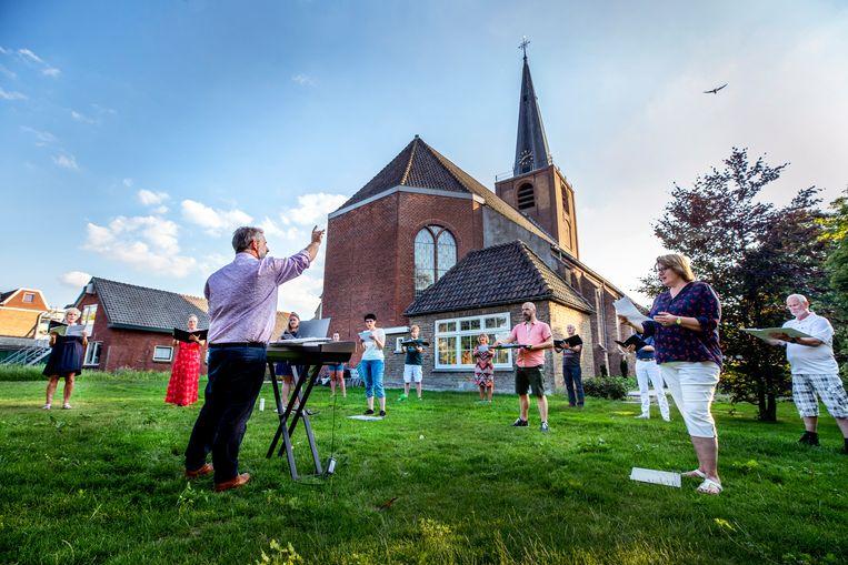 The New Choral Singers repeteren in de tuin van de kerk in Wateringen. Beeld Raymond Rutting