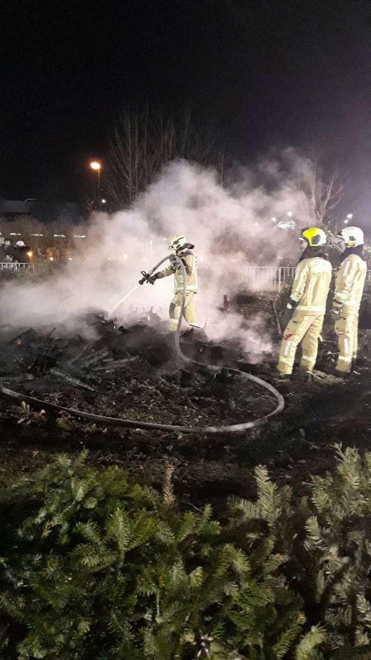 De brandweer bluste de brandende hoop kerstbomen.