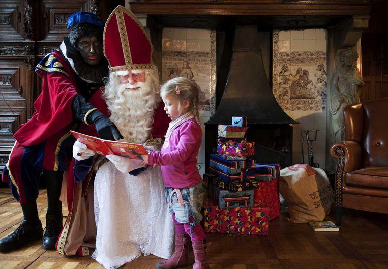 Een kindje wordt ontvangen door Sinterklaas en Zwarte Piet Beeld anp