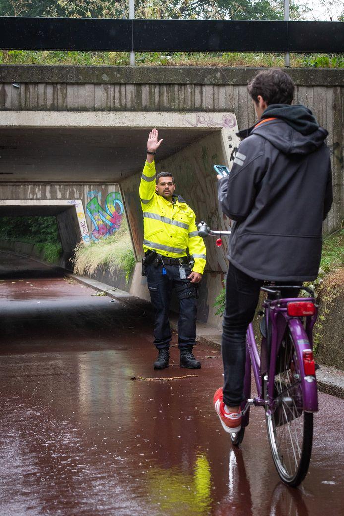Breda - Pix4Profs/René Schotanus. Politieman houdt appende jongen op de fiets aan.