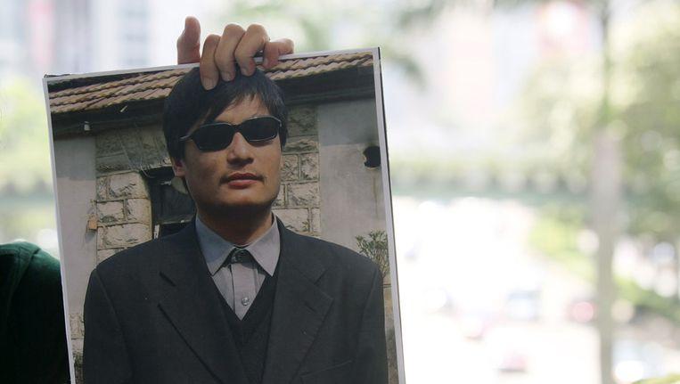 Een Chinese mensenrechtenactivist houdt een poster in de hoogte met een afbeelding van Chen Beeld ap