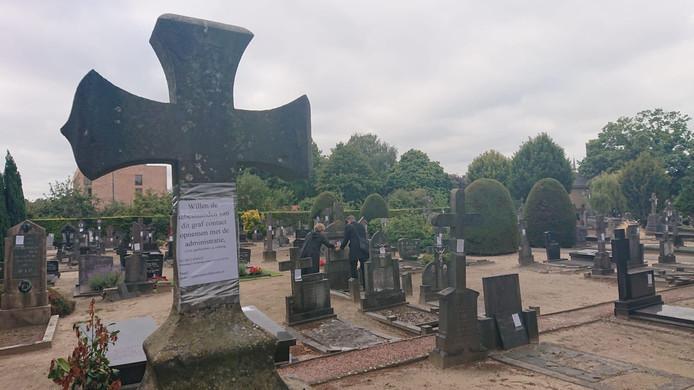 Op honderden graven worden briefjes geplakt.