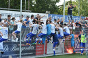 De spelers van Hoek klimmen in de hekken en vieren de promotie met de aanhang.