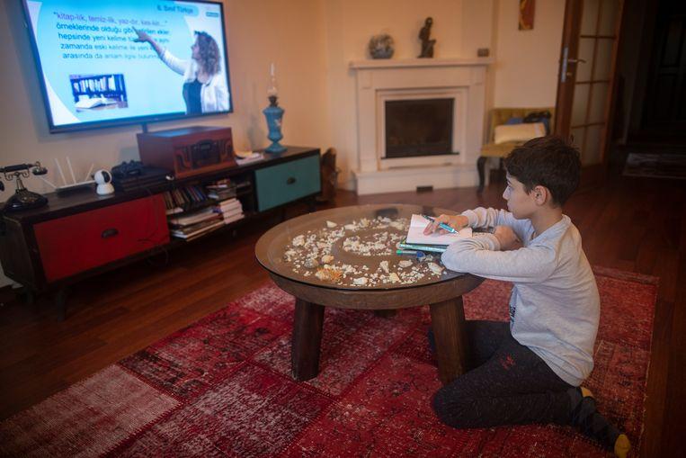 In Turkije krijgt een leerling les via het televisiescherm.   Beeld EPA
