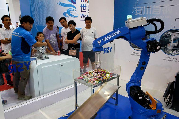 De Chinese fabrikant Yaskawa demonstreert een industriële robot aan bezoekers van de World Robot Conference in Beijing. Beeld AP